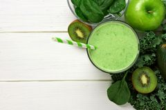 Green smoothie above view with ingredients against white wood. Green smoothie above view with kale, avocado, spinach, apple and kiwi against a white wood Stock Images