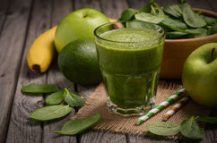Green smoothie with apple, banana, avocado and spinach on a wooden rustic background. Stock Images