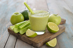 Green smoothie. Smoothie of green apple, celery, avocado and lime on wooden background Royalty Free Stock Images