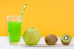 Green smoothie with apple and kiwi on a white wooden table and yellow background Royalty Free Stock Image
