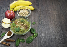 Green smoothie with apples, spinach, banana, germinated buckwheat and cinnamon on a dark wooden background. Green smoothie with apples, spinach, banana stock images