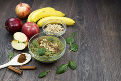 Green smoothie with apples, spinach, banana, germinated buckwheat and cinnamon on a dark wooden background. Green smoothie with apples, spinach, banana royalty free stock image