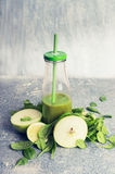 Green smoothie in bottle and ingredients: apple and spinach, on rustic background, front view Stock Image