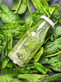 Green smoothie in bottle  lies on fresh spinach background Stock Photo