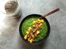 Green smoothie bowl with chopped mango and chia seeds Royalty Free Stock Photos