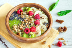 Green smoothie bowl. Healthy breakfast green smoothie bowl topped with fruits, nuts, berries and seeds over rustic wooden background Royalty Free Stock Images