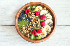 Green smoothie bowl. Healthy breakfast green smoothie bowl topped with fruits, nuts, berries and seeds over rustic wooden background Stock Photo