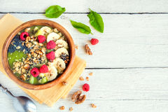 Green smoothie bowl. Healthy breakfast green smoothie bowl topped with fruits, nuts, berries and seeds over white wooden background with copy space Stock Images