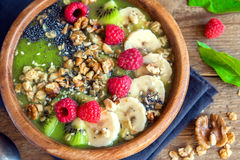 Green smoothie bowl. Healthy breakfast green smoothie bowl topped with fruits, nuts, berries and seeds over wooden background close up Royalty Free Stock Image