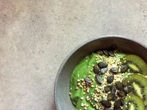 Green smoothie bowl with hemp seeds, buckwheat, pumpkin seeds and kiwifruit. A thick green smoothie served in a bowl and topped with slices of kiwifruit, toasted Stock Images