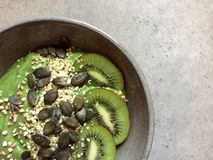 Green smoothie bowl with hemp seeds, buckwheat, pumpkin seeds and kiwifruit. A thick green smoothie served in a bowl and topped with slices of kiwifruit, toasted Stock Photo