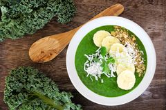Green smoothie bowl with kale, bananas, granola, and coconut Royalty Free Stock Photos