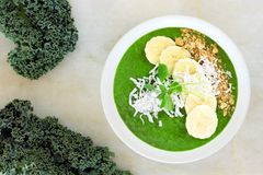Green smoothie bowl with kale, bananas, granola, and coconut Stock Image