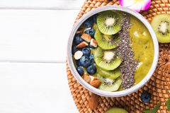 Green smoothie bowl with kiwi, blueberry and chia seeds royalty free stock photo