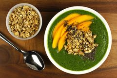Green smoothie bowl with mangoes, granola and chia seeds. Green smoothie bowl with mangoes, granola, almonds and chia seeds, overhead view on wood Stock Photography