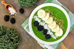 Green smoothie bowl overhead scene on granite Royalty Free Stock Photo