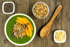 Green smoothie bowl overhead scene on wood Stock Photo