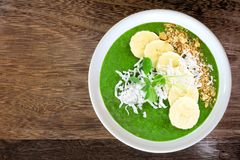 Green smoothie bowl overhead view on rustic wood Royalty Free Stock Photos