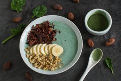 A green smoothie bowl with raw ingredients. A green smoothie bowl with spinach, spirulina powder bananas, muesli, and cocoa nibs royalty free stock images