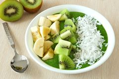 Green smoothie bowl with spoon on a table Royalty Free Stock Image