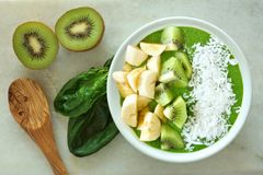 Green smoothie bowl with spoon on white marble Stock Images