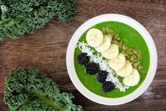 Green smoothie bowl superfoods on rustic wood Royalty Free Stock Images