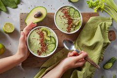Green Smoothie Bowl With Fresh Kiwi, Flaxseeds, Cucumber And Avocado In The Female Hands Stock Photos
