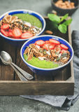 Green smoothie bowls with seeds, nuts, fruit and fresh berries Stock Photography