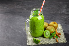 Green smoothie drink in a big mason jar. Refreshing beverage with fresh cut green kiwis and cinnamon on a gray. Close-up of a green kiwi beverage on a gray stone stock images