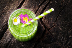 Green smoothie, edible blossoms. Green smoothie with edible blossoms royalty free stock image