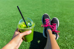 Green smoothie fitness running shoes feet selfie. Green smoothie woman drinking plastic cup breakfast takeaway juice to go after morning run in summer park Stock Image