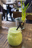 Green smoothie and flowers Royalty Free Stock Photos
