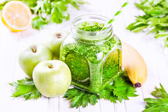 Green smoothie. Fresh green smoothie with banana, apples, celery and lemon on white table stock photo
