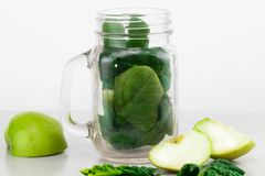 Green smoothie in glass jar with fresh organic green vegetables Stock Images