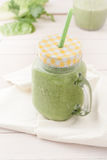 Green smoothie in a glass jar with lid and a straw Royalty Free Stock Images