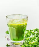 Green smoothie glass and kale on light background, close up. Royalty Free Stock Image