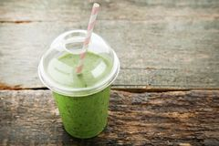 Green smoothie. In plastic cup on wooden table stock photography