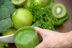 Green smoothie in hand Stock Image