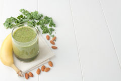 Green smoothie, ingredients include bananas, fresh kale and almonds. Green smoothie on white background, ingredients include bananas, fresh kale and almonds Royalty Free Stock Photo