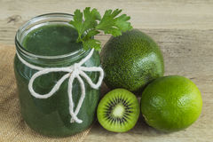 Green smoothie in a jam jar with ingredients royalty free stock photo