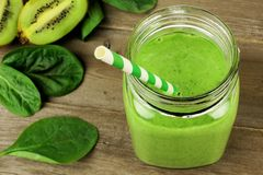 Green smoothie in a jar downward view. Healthy green smoothie with spinach and kiwi in a jar mug on wood, downward view stock photo