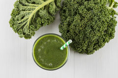 Green smoothie with kale leaves and straw Royalty Free Stock Photo