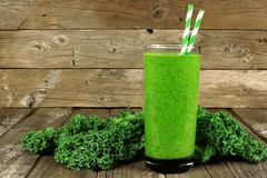 Green smoothie with kale on wood background. Healthy green smoothie with kale in a glass against a rustic wood background Stock Photo