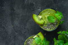 Green smoothie with kiwi, chia, mint. Copy space, top view. Green smoothie with kiwi, chia, mint on dark background with spoons. Copy space, top view Royalty Free Stock Image