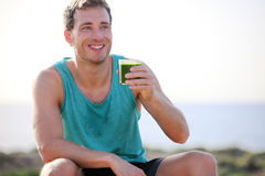 Green smoothie man drinking vegetable juice. After running sport fitness training. Healthy eating lifestyle concept with young man outdoors royalty free stock images