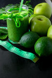 Green smoothie near centimeter and  ingredients for it on black wooden background. Diet. Detox. Healthy drink. Royalty Free Stock Photos