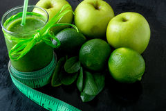 Green smoothie near centimeter and  ingredients for it on black wooden background. Diet. Detox. Healthy drink. Royalty Free Stock Images