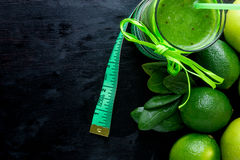 Green smoothie near centimeter ingredients for it on black wooden background. Diet. Detox. Healthy drink. Top view. Stock Images