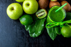 Green smoothie near ingredients for it on black wooden background. Apple, lime, spinach, kiwi. Detox. Healthy drink. Top view. Cop Stock Photo
