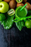 Green smoothie near ingredients for it on black wooden background. Apple, lime, spinach, kiwi. Detox. Healthy drink. Top view. Cop Stock Image